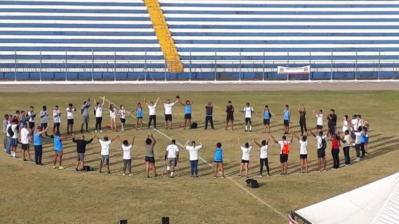 Integrantes do atletismo em oração logo após o encerramento das provas.