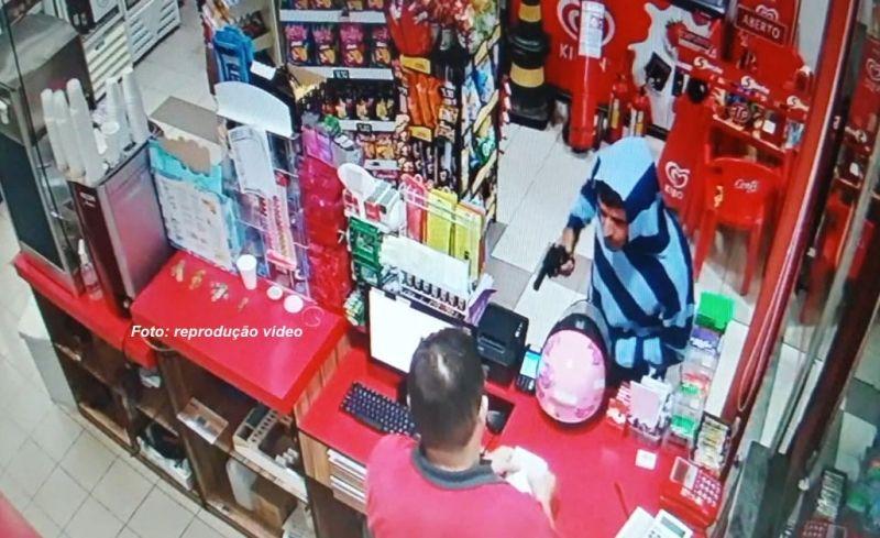 Um dos criminosos rende o funcionário da loja de conveniência armado com um revólver