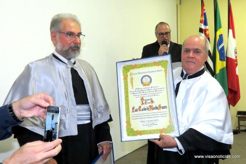 Dr. Luiz Carlos recebe o título do presidente do Conselho Universitário, professor Luiz Fernando Cardoso.