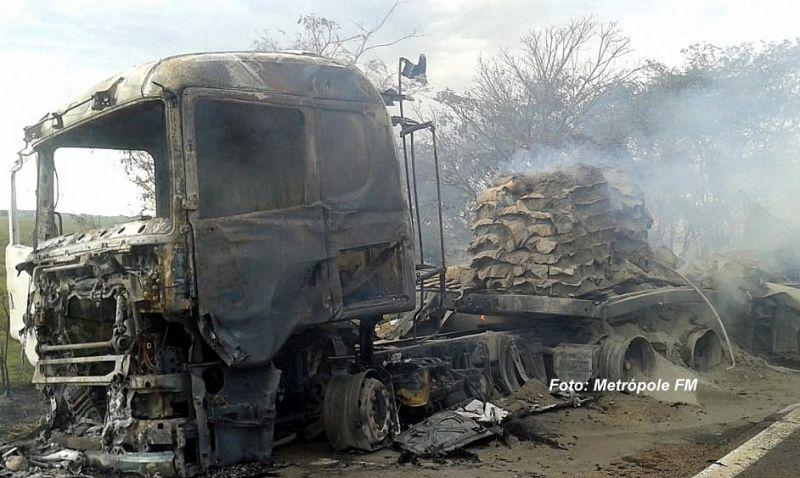 As duas carretas ficaram destruídas após a batida e pegarem fogo.