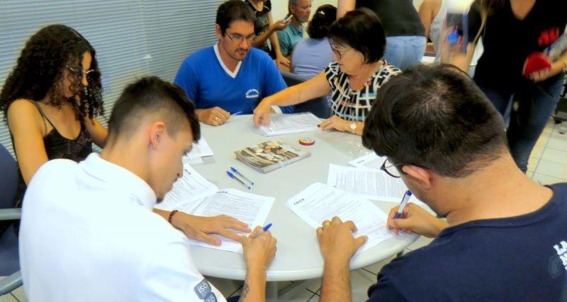 Os 50 mutuários durante a assinatura dos contratos na Caixa Federal em Pompeia
