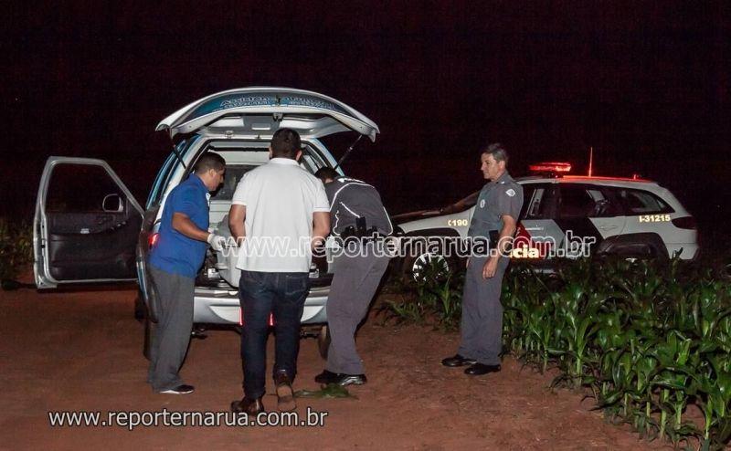 O corpo da vítima de homicídio é levado pela funerária após a perícia.