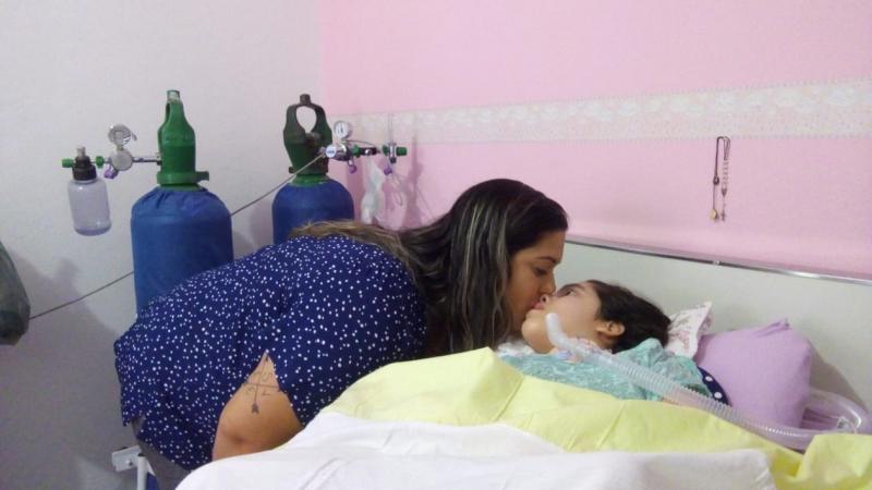 """Menina com paralisia tem a vida ligada a tomadas, mãe desabafa: """"Se faltar luz, minha filha morre"""""""